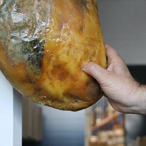 Primo piano del pollice che affonda nel grasso di un prosciutto iberico